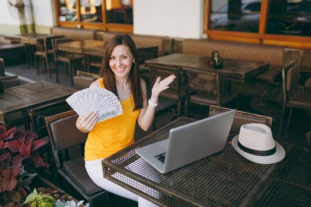 Mujer en el café de la cafetería de la calle al aire libre sentado con un moderno ordenador portátil, tiene en la mano un montón de billetes de dólares