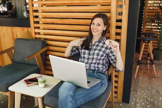Mujer en el café de la cafetería de la calle al aire libre sentado con un ordenador portátil, mantenga bitcoin, moneda de metal de color dorado