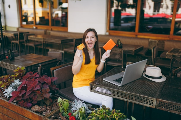 Mujer en el café de la calle al aire libre sentado a la mesa con un moderno ordenador portátil, tiene en la mano la tarjeta de crédito bancaria y el pasaporte
