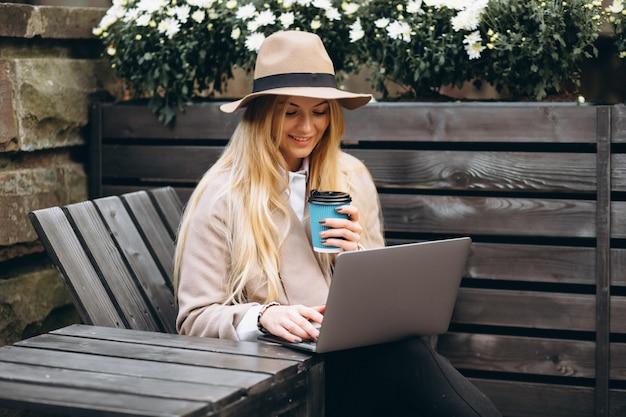 Mujer en café de consumición del sombrero y trabajando en la computadora portátil afuera