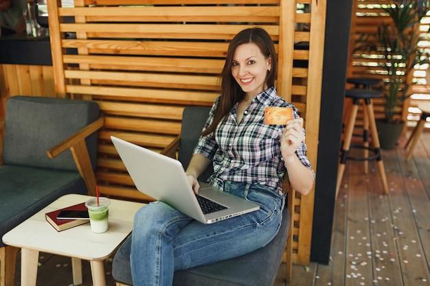 Mujer en el café de madera de la cafetería de verano de la calle al aire libre sentado trabajando en la computadora portátil, mantenga la tarjeta de crédito bancaria relajándose durante el tiempo libre
