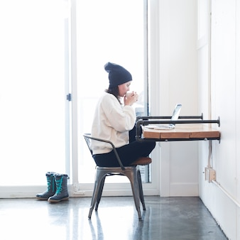 Mujer con café y portátil en la mesa