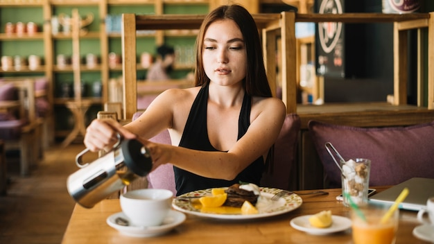 Mujer en el café que vierte el café en la taza