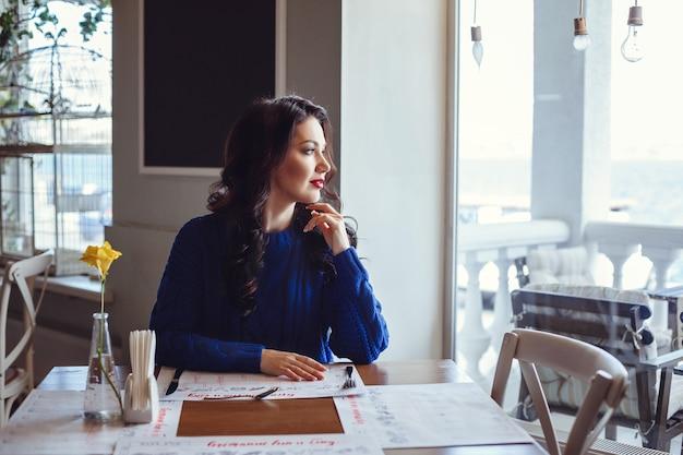 Mujer en el café se sienta en una mesa, bebe café y mira la ventana. mujer con lápiz labial rojo y suéter azul está esperando una reunión, hablando por teléfono y sonriendo mucho.