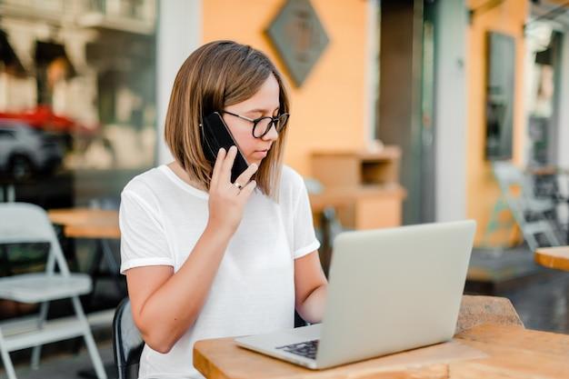 Mujer en café con teléfono y computadora portátil