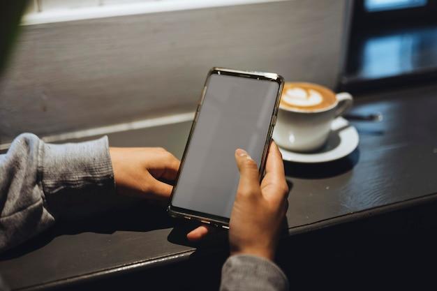Mujer en un café con un teléfono móvil