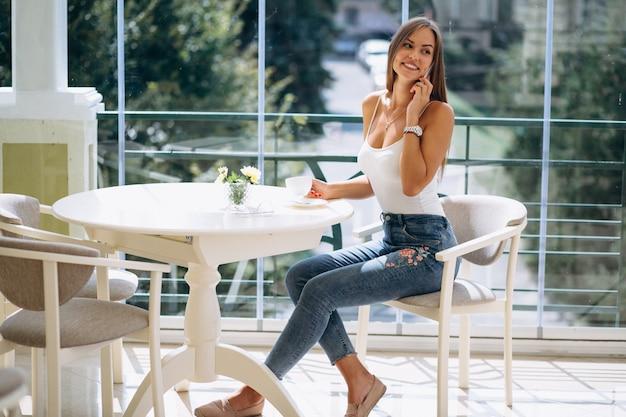 Mujer en café tomando café y hablando por teléfono
