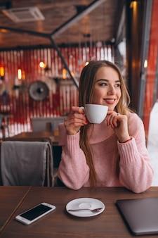 Mujer en café tomando café y trabajando en una computadora