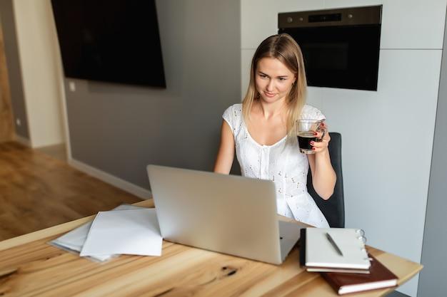 Mujer con café trabajando en la computadora portátil en la oficina en casa