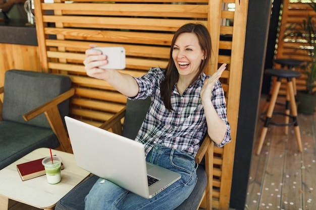 Mujer en la cafetería de verano de la calle al aire libre de madera sentado con la computadora portátil, haciendo selfie en teléfono móvil, relajándose durante el tiempo libre. oficina móvil