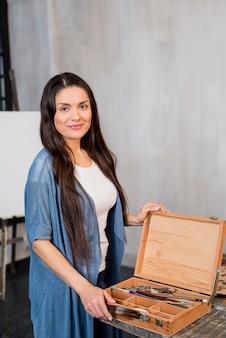 Mujer con caja de madera de materiales de pintura
