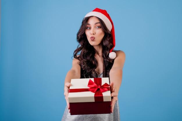Mujer con caja de regalo con gorro de papá noel