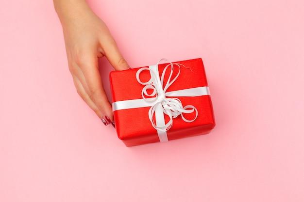 Mujer con caja de regalo sobre fondo de color