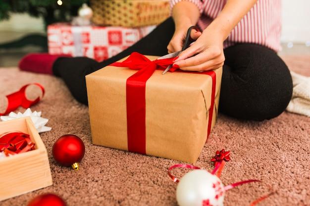 Mujer con caja de regalo y tijeras cerca de arcos decorativos, bolas y cinta en la alfombra