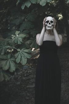 Mujer con calavera blanca en matorral
