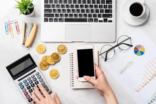 Una mujer está calculando la tarifa, las ganancias y haciendo un pago en línea en una mesa de oficina de mármol moderna, maqueta, vista superior, espacio de copia, plano