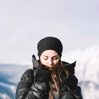 Mujer calentándose las manos con los ojos cerrados