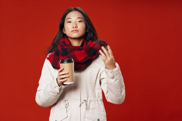 Mujer caliente taza de bebida café bufanda a cuadros invierno rojo modelo de espacio aislado estilo elegante