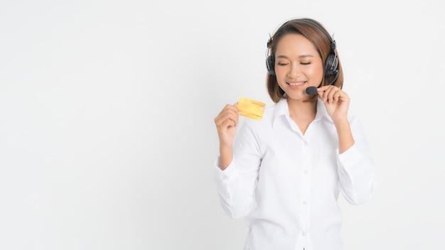 Mujer call center con auriculares y tarjeta de crédito.