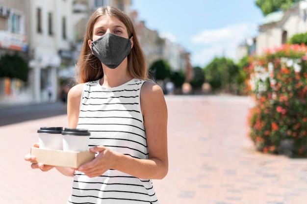 Mujer en la calle con café con máscara