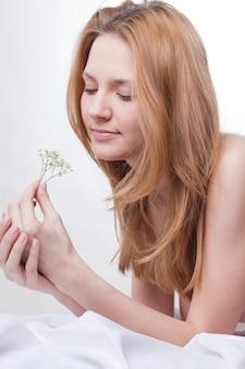 Mujer en la cama con una flor