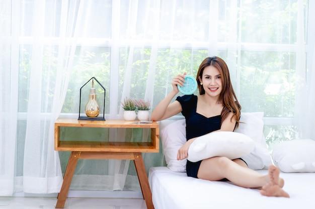 Mujer y cama por la mañana despierta y sonríe felizmente buen concepto de descanso