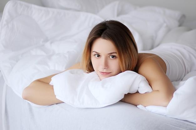 La mujer en la cama con los ojos abiertos de insomnio no puede dormir durante la ansiedad durante el día