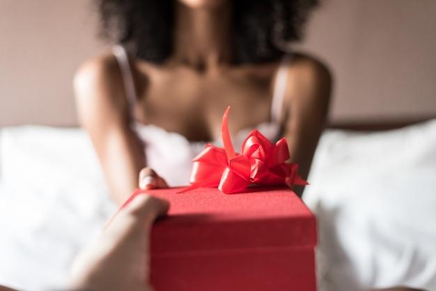 Mujer en la cama con un regalo en san valentín o cumpleaños