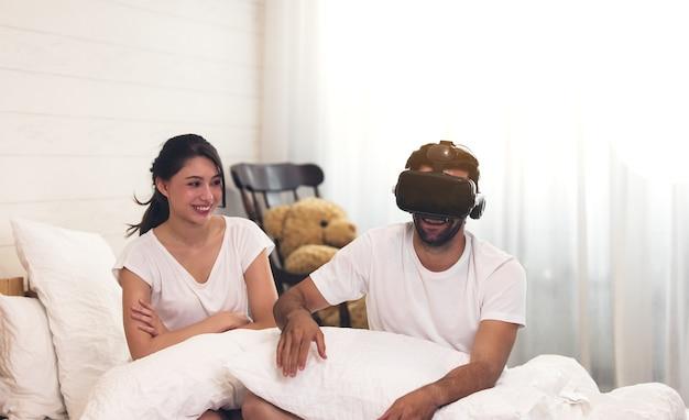 Mujer en la cama con su marido hombre con cabello corto oscuro y barba de 3 días usando su cabezal vr establece video de juegos con gafas 3d, divirtiéndose.