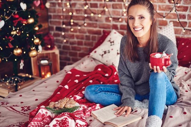 Mujer en la cama con taza de chocolate leyendo un libro