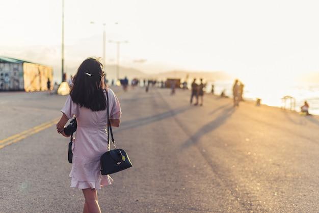 Mujer con una cámara caminando cerca de una playa en un día soleado