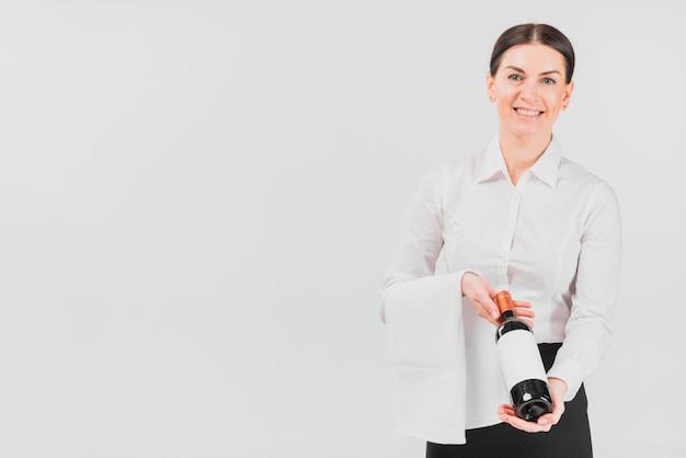 Mujer de camarera ofreciendo botella de vino