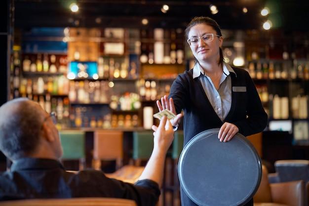 Mujer de la camarera recibe una propina