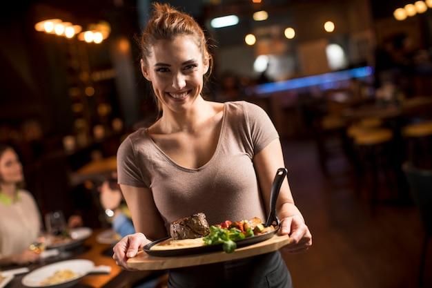 Mujer de camarero sirviendo a un grupo de amigos con comida en el restaurante