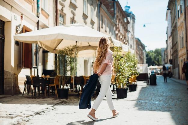 La mujer camina antes del café de la calle