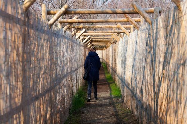 Mujer camina por un sendero con barreras de seguridad hechas de cañas
