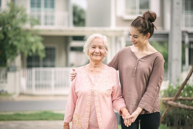 Mujer caminando y abrazando asiática anciana