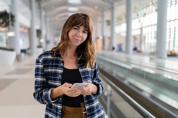 Mujer caminando por el aeropuerto con su dispositivo de teléfono inteligente.