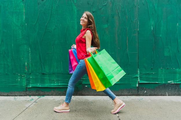 Mujer caminando con bolsas de compras en el fondo de la pared verde