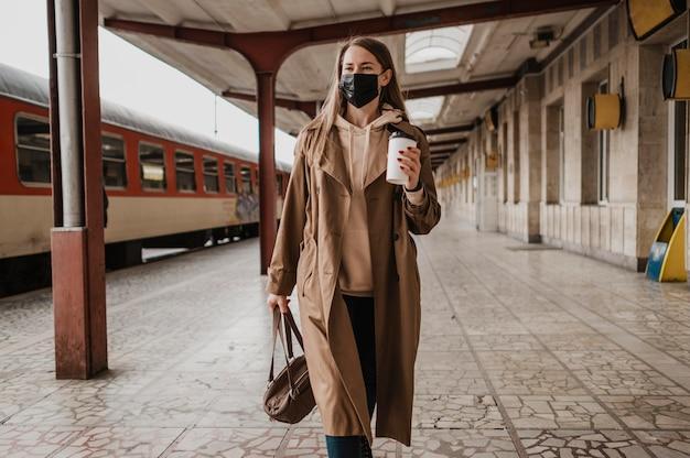 Mujer caminando con un café en una estación de tren