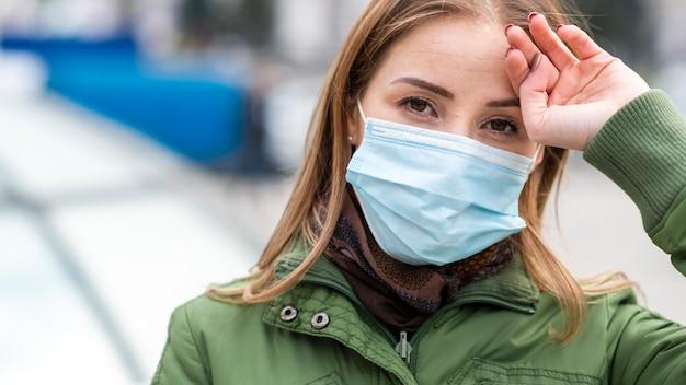 Mujer caminando por la calle y con una máscara
