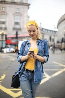 Mujer caminando en la calle, revisando su teléfono