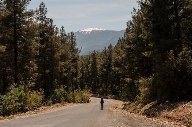 Mujer caminando en el camino con mochila de senderismo