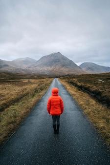 Mujer caminando por una carretera en glen etive, escocia