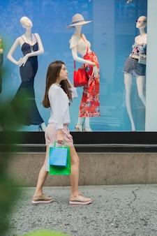 Mujer caminando cerca de la ventana de la tienda
