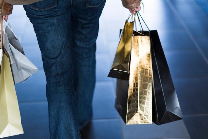 Mujer caminando con bolsas de compras brillantes