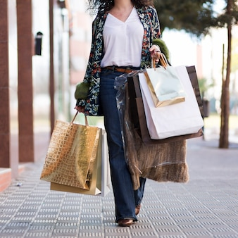 Mujer caminando en la calle con bolsas de compras