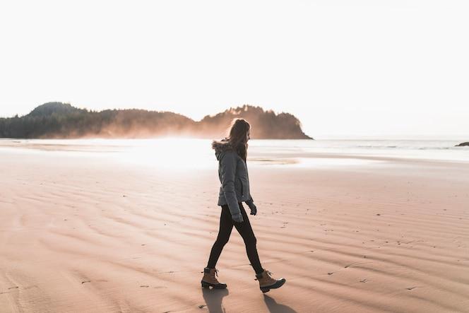 Mujer caminando en la orilla del mar