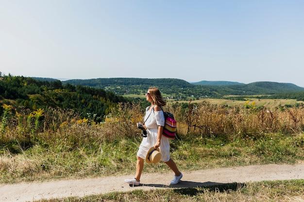 Mujer caminando de lado con paisaje como fondo