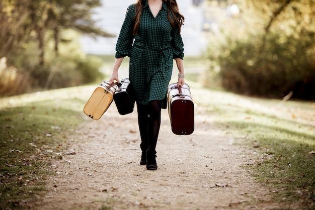 Mujer caminando mientras sostiene su vieja maleta con un fondo borroso